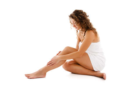 waxed legs: Woman massaging legs sitting on white background Stock Photo