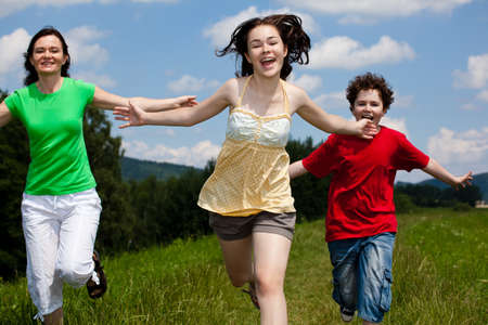 Active family - mother and kids running, jumping outdoor photo