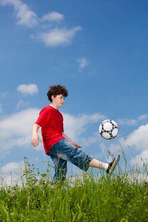 kids playground: Boy playing football outdoor Stock Photo