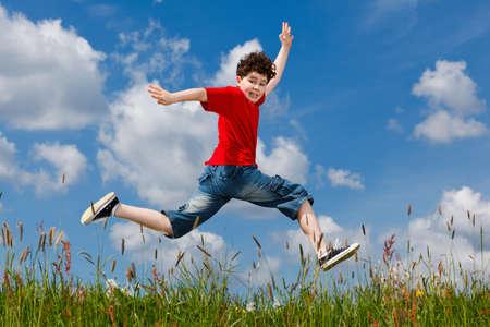 ni�o corriendo: Chico saltando, corriendo contra el cielo azul