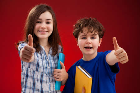 Students showing OK sign on red background photo