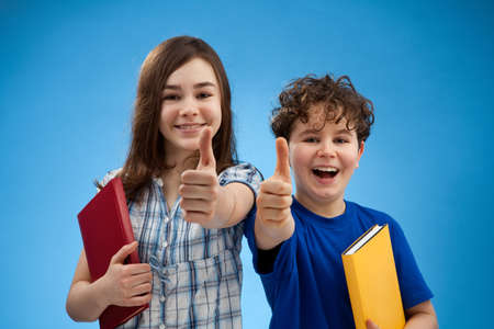 schoolgirl: Students showing OK sign on blue background Stock Photo