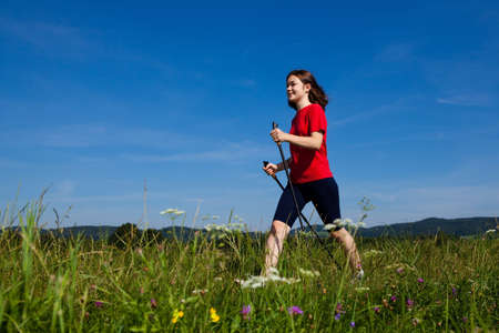Nordic walking - active girl exercising outdoor photo