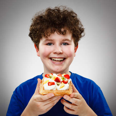 13 14 years: Boy eating cake with cream and fruits Stock Photo