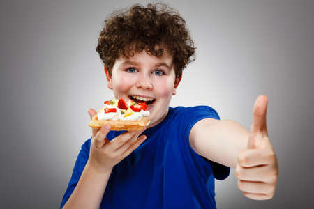 13 14 years: Boy eating cake with cream and fruits , OK sign Stock Photo