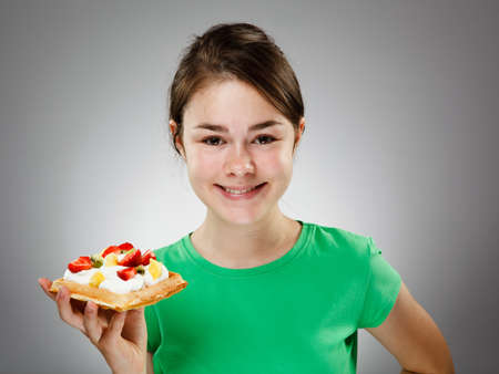 13 14 years: Girl eating cake with cream and fruits