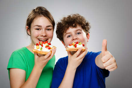 13 14 years: Girl and boy eating cake with cream and fruits , OK sign Stock Photo