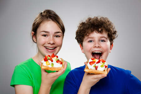 Kids eating cake with cream and fruits photo