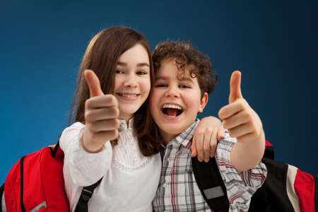 children studying: Students showing OK sign on blue background Stock Photo