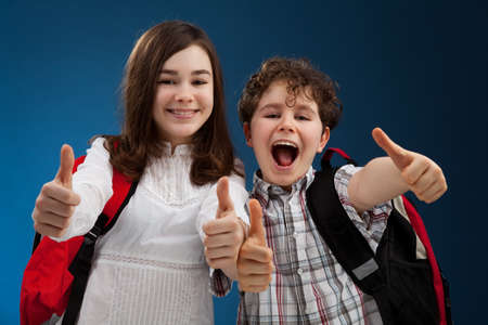 Students showing OK sign on blue background photo