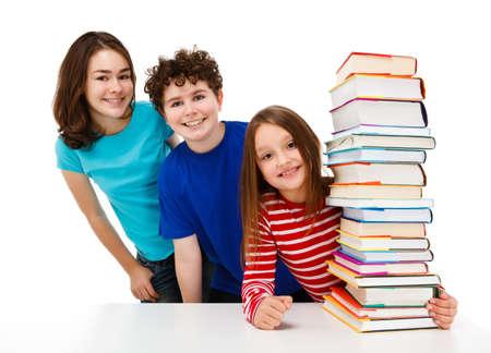Students peeking behind pile of books on white Stock Photo - 14326470