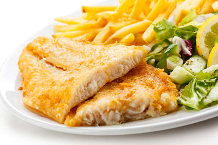 Fish dish - fried fish fillet, French fries with vegetables Imagens