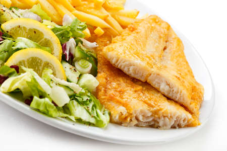 Fish dish - fried fish fillet, French fries with vegetables photo