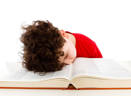 Tired kid sleeping on book isolated on white background  photo