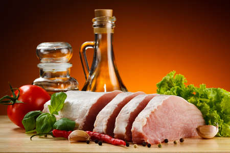 Raw pork on cutting board and vegetables photo