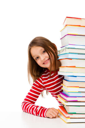bambini che leggono: Ragazza sbirciando dietro una pila di libri su sfondo bianco Archivio Fotografico