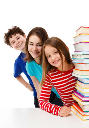 Students peeking behind pile of books on white photo