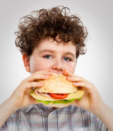Boy eating big sandwich photo