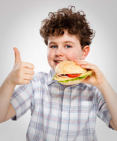 Boy eating big sandwich showing OK sign photo