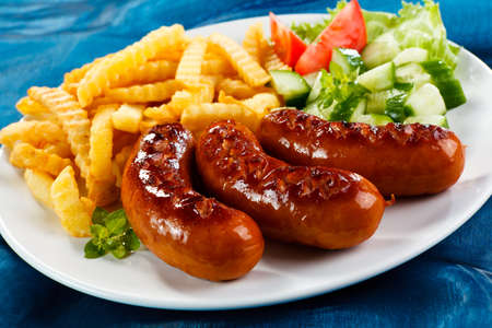 Grilled sausages, French fries and vegetables photo