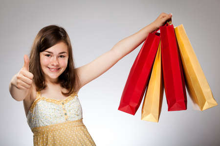 Girl holding shopping bags showing ok sign photo