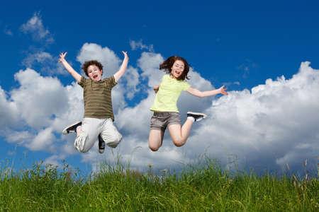 niños jugando: Chica y chico corriendo, saltando al aire libre