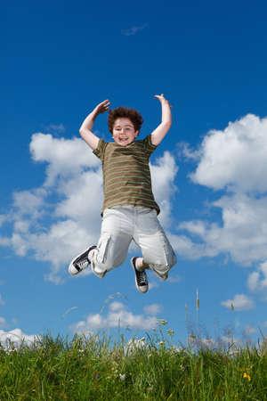 ni�o saltando: Boy salto, corriendo contra el cielo azul