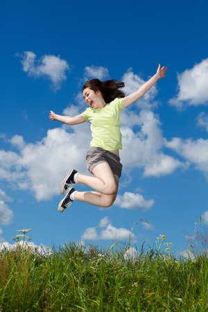 persona saltando: Chica saltando, corriendo contra el cielo azul Foto de archivo