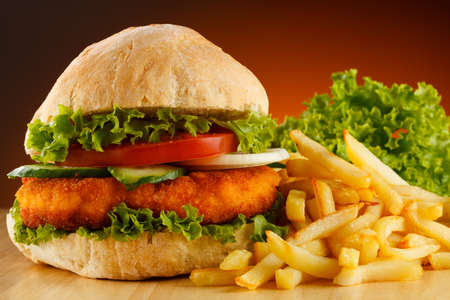 Big hamburger, French fries and vegetables Stock Photo - 15221979