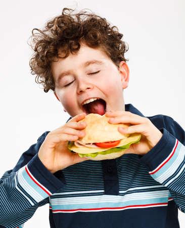 큰 샌드위치를 먹는 소년