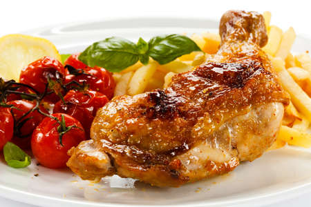 chicken leg: Grilled chicken leg, chips and vegetables Stock Photo