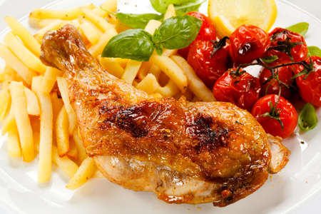Grilled chicken leg, chips and vegetables photo