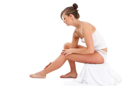 Woman massaging legs sitting on white background photo