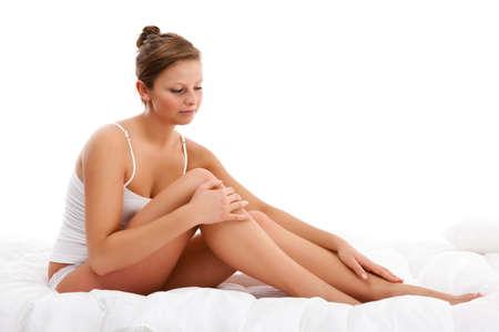 massage jambe: Femme jambes massage assis sur fond blanc