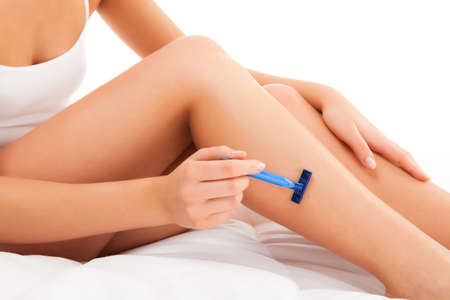Woman shaving legs sitting on white background photo