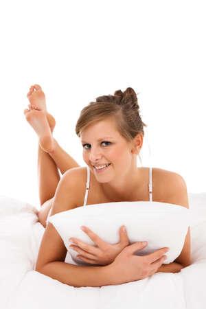 Donna sdraiata sul letto isolato su sfondo bianco