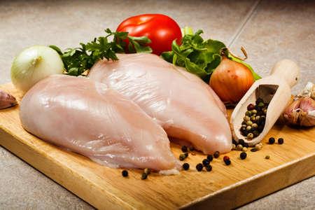 Poitrines de poulet cru sur une planche à découper