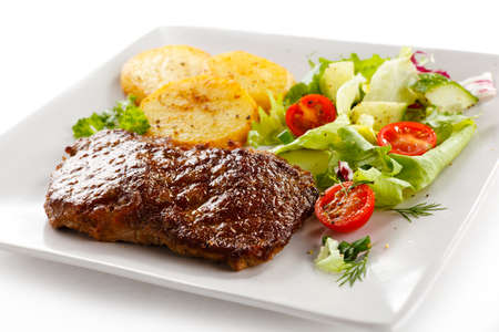 pork chop: Grilled beefsteak, baked potatoes and vegetables Stock Photo