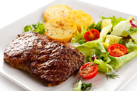 steak plate: Grilled beefsteak, baked potatoes and vegetables Stock Photo