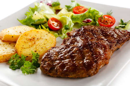 barbecued: Grilled beefsteak, baked potatoes and vegetables Stock Photo