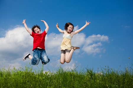 女の子と男の子のランニング、ジャンプ屋外 写真素材
