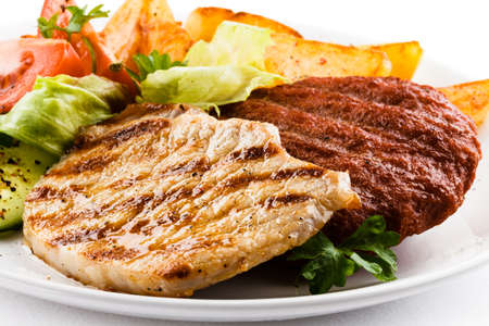 baked potatoes: Grilled steaks, baked potatoes and vegetable salad Stock Photo