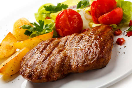 grilled potato: Grilled steak, fried potatoes and vegetable salad Stock Photo