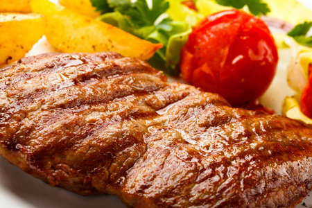 Grilled steak, fried potatoes and vegetable salad photo