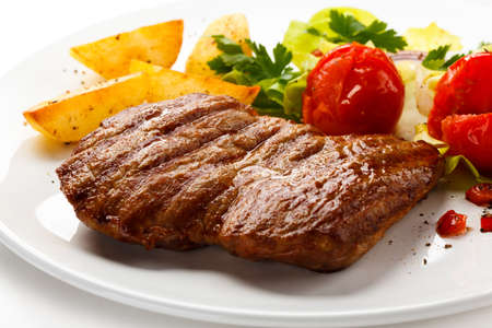 rumpsteak: Grilled steak, fried potatoes and vegetable salad Stock Photo
