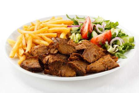 kebab: Grilled meat with French fries and vegetables