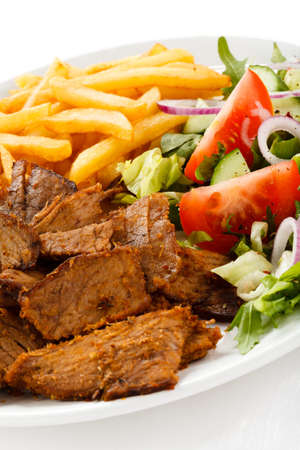 chicken kebab: Grilled meat with French fries and vegetables