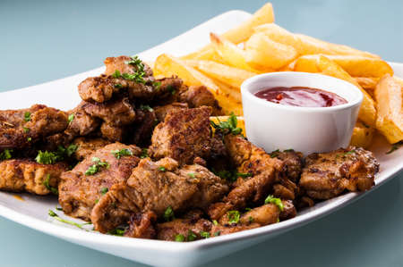 Grilled meat with French fries photo