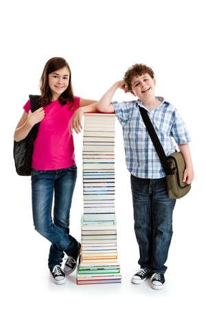 niño con mochila: Los estudiantes que se colocan cerca de la pila de libros en blanco