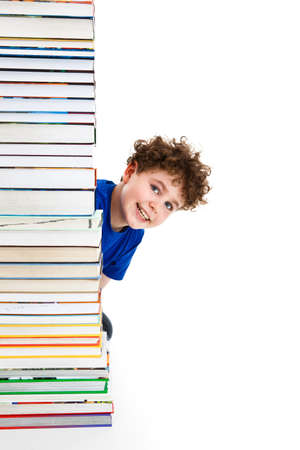 Boy behind pile of books isolated on white background photo